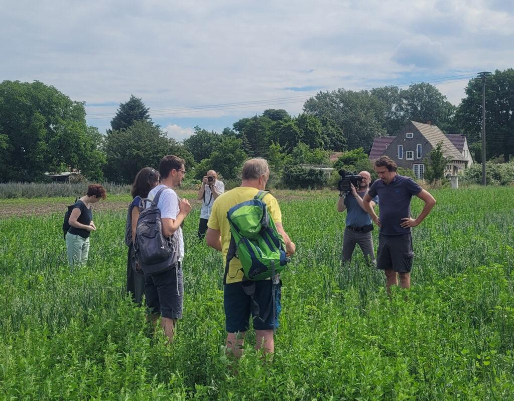 Johannis Erz, Bio-Landwirt aus Rathstock auf einem vom ihm bewirtschafteten Acker in Reitwein im Gespräch mit Benjamin Raschke.